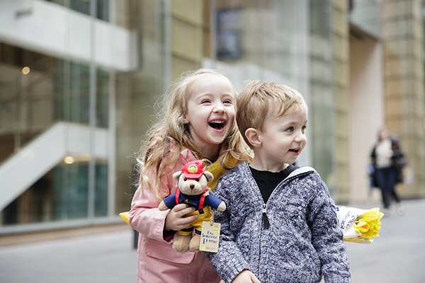 Two young children in Martin Place holding a Dougal bear and a bunch of daffodils